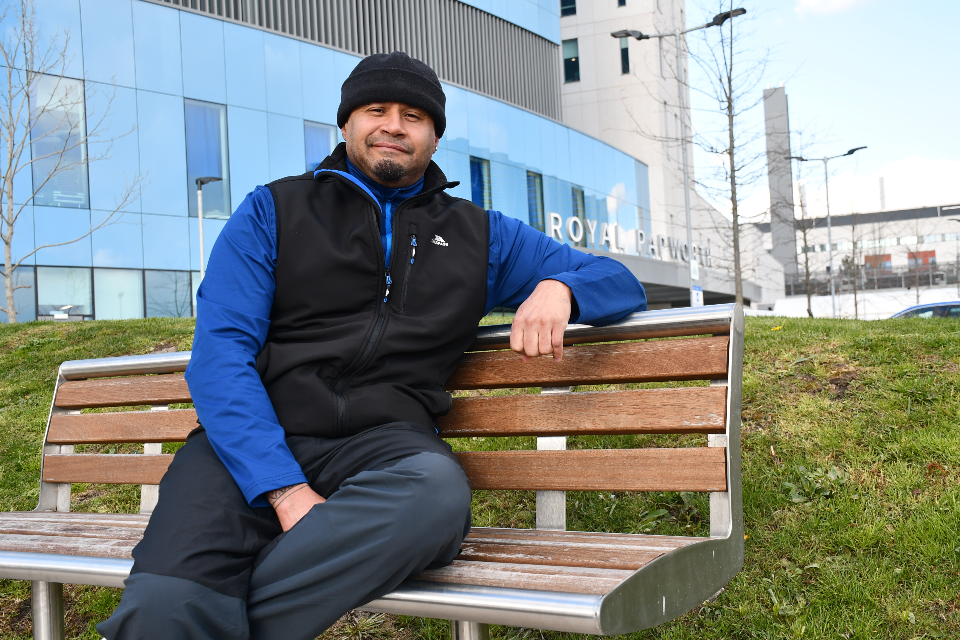 A man in a blue top and black body warmer sits on a bench outside a hospital.