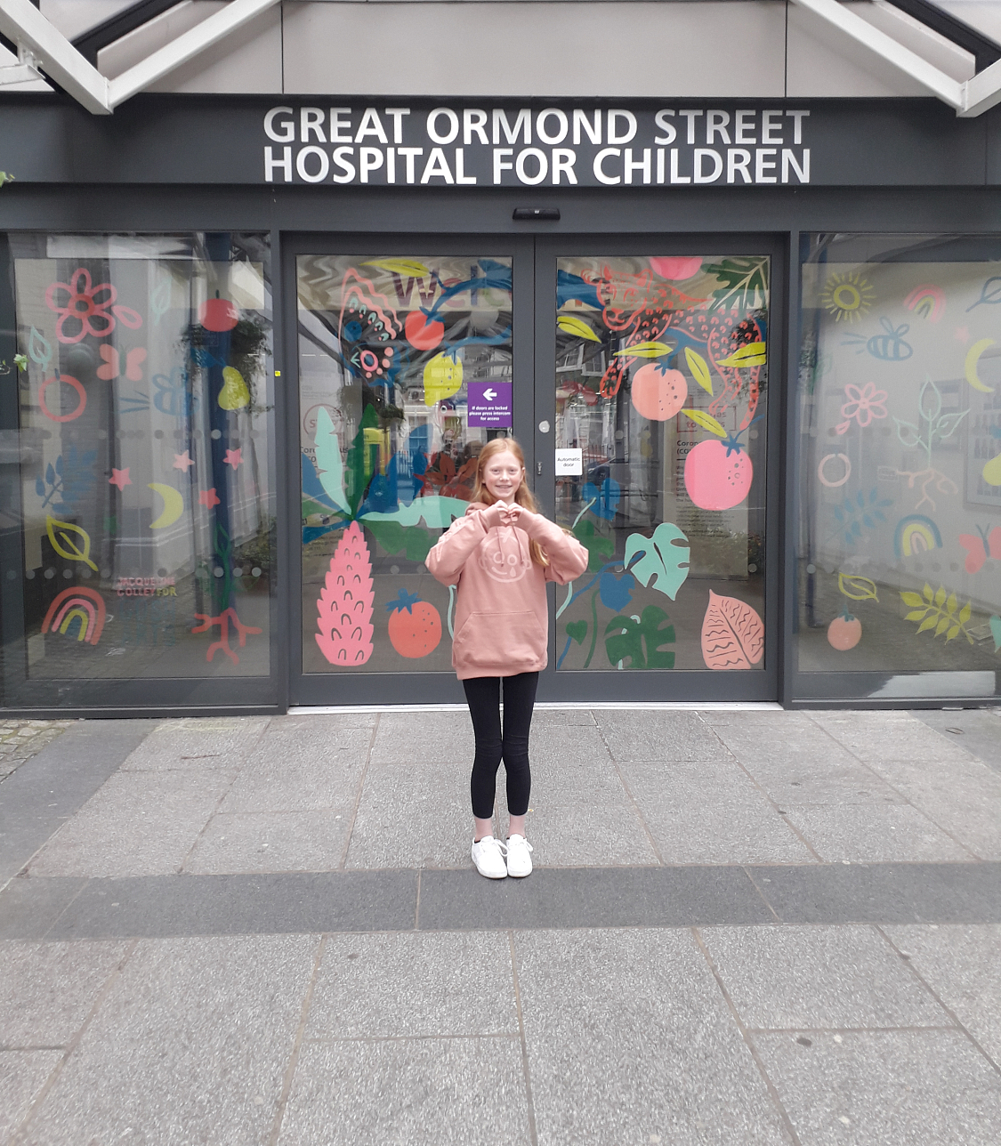 A girl stands outside Great Ormond Street Hospital for Children